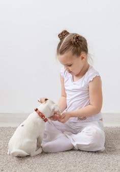 Concepto de mascotas y perros de la infancia pequeño cachorro y niña en camisa blanca divirtiéndose