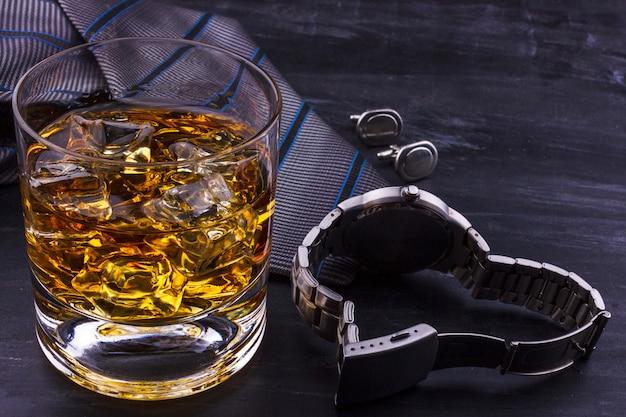 Concepto masculino para el día del padre. corbata, relojes, gemelos y un vaso de whisky con hielo.