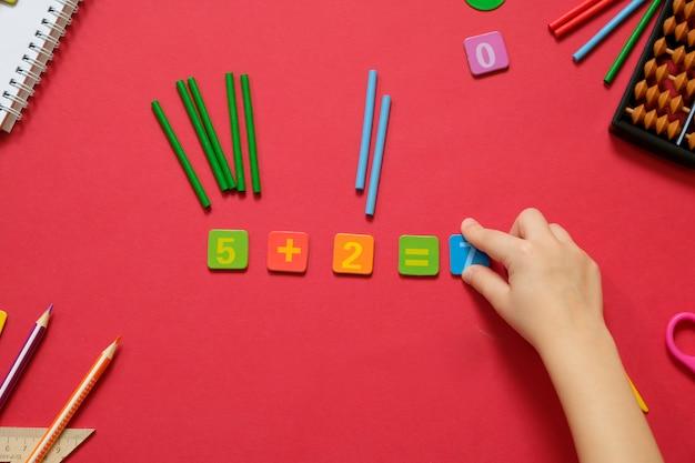 Concepto matemático: bolígrafos y lápices de colores, números, palos de cálculo