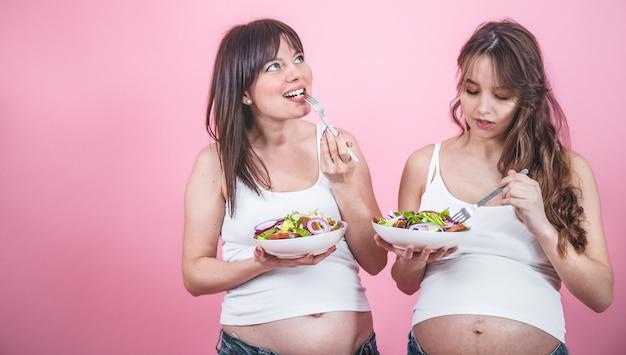 Concepto de maternidad, dos mujeres embarazadas comiendo ensalada fresca