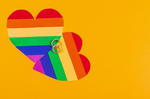 Concepto de matrimonio gay con la bandera del arco iris y anillos