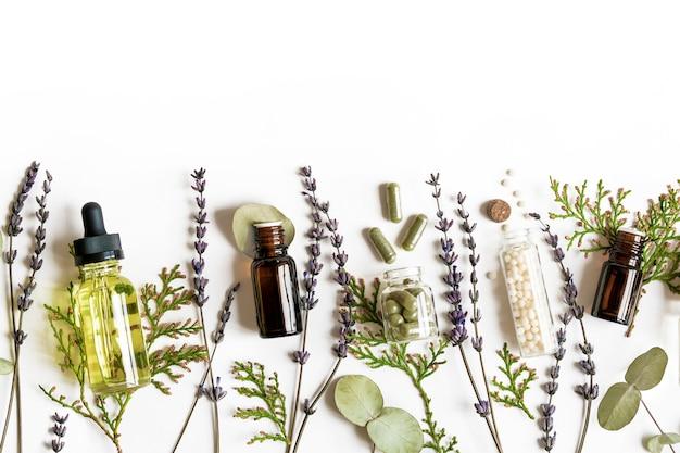 Concepto de medicina alternativa ecológica de la homeopatía: píldoras de homeopatía clásica, tuya, eucalipto, aceite esencial de lavanda y aceite aromático y hierbas curativas y en la pared blanca. flatlay vista superior. copyspace