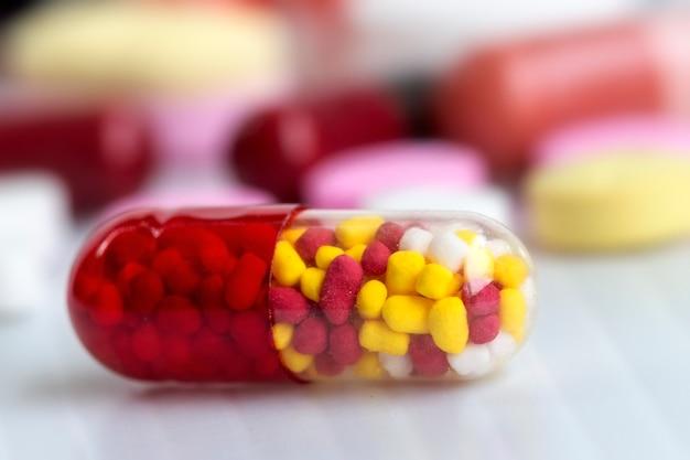 Concepto de medicina; cápsula de colores y píldora sobre el fondo blanco