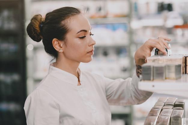 Concepto de medicina, farmacia, salud y personas. farmacéutico de sexo femenino que toma los medicamentos del estante.
