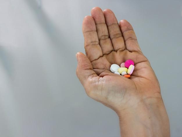 Concepto de medicina; pastillas en mano aislado en gris borrosa