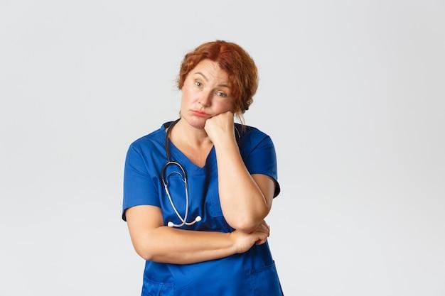 Concepto de medicina, salud y coronavirus. enfermera de la casa de retiro de mediana edad aburrida y cansada, trabajador médico en la clínica o médico en matorrales con aspecto poco divertido, sentado en una reunión aburrida.