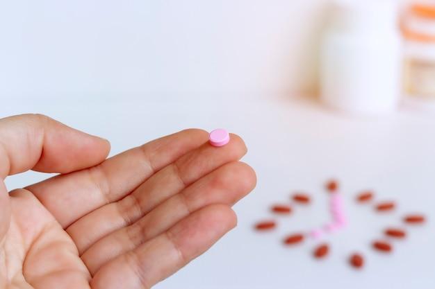 Concepto de medicina; tomar un medicamento a tiempo todos los días, la píldora rosa está en el dedo.