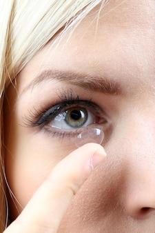Concepto de medicina y visión - mujer joven con lentes de contacto, cerrar