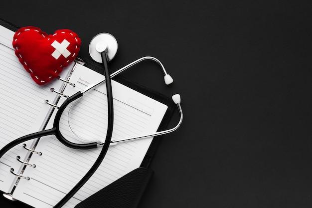 Concepto médico blanco y negro con estetoscopio y corazón rojo