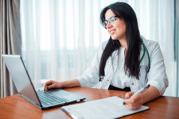 Concepto de médico de familia, especialista se sienta en la computadora portátil