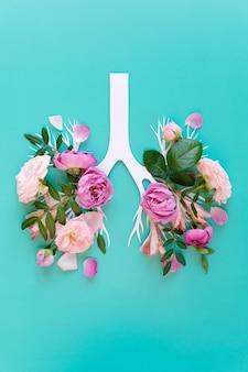 Concepto médico de flores de color lila rosa en forma de pulmones humanos sobre fondo azul. inflamación del concepto de pulmones, epidemia viral. vista plana endecha, superior. daño de fumar