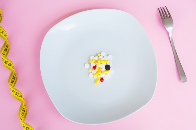Concepto médico píldoras de colores y cápsulas en un plato con un tenedor. tema de farmacia, píldoras de cápsulas con antibióticos medicinales en paquetes