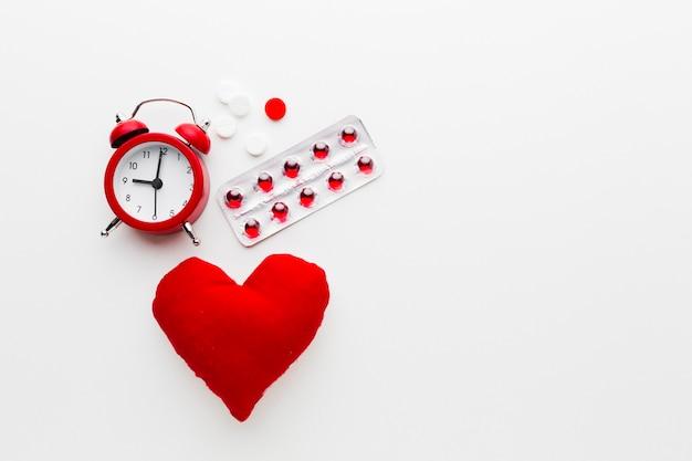 Concepto médico rojo y blanco con reloj y pastillas
