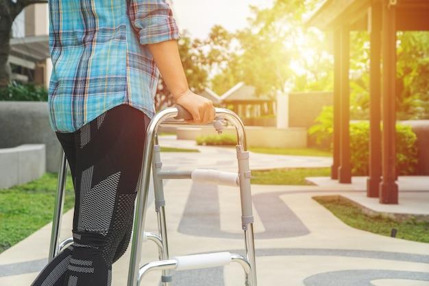 Concepto médico y de salud, mujer caminando con un andador de aluminio en un parque.