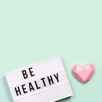 Concepto médico y sanitario. caja de luz con palabras be healthy y corazón de papel rosa