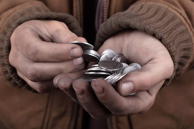 Concepto de mendigo pobre hombre pide asistencia en efectivo. monedas de plata en las palmas.