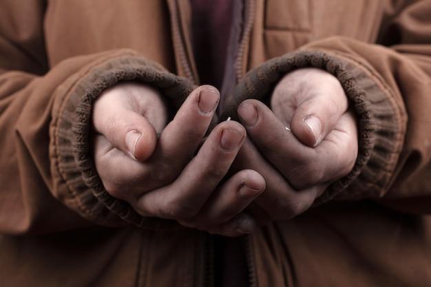 Concepto de mendigo pobre hombre pide asistencia en efectivo. monedas de plata en el primer plano de las palmas