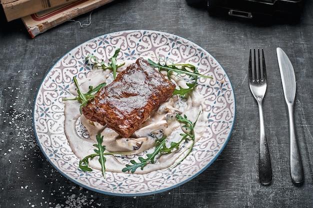 Concepto: menú de restaurante, comida sana, casera, gourmet, glotonería. plato con filete y salsa de champiñones sobre una mesa de madera desgastada. vista de arriba hacia abajo