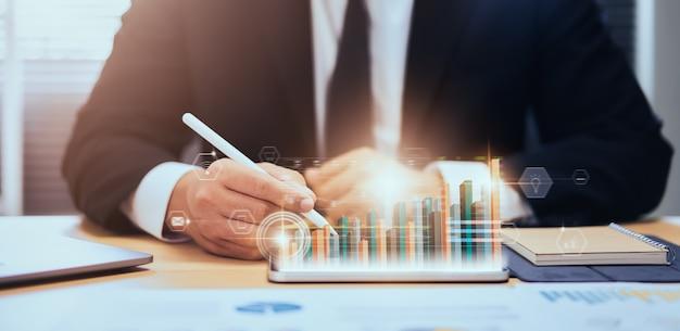 Concepto de mercado de valores, comerciante de mano de hombre de negocios presione tableta digital con línea de vela de análisis de gráficos en la mesa en la oficina, diagramas en la pantalla.