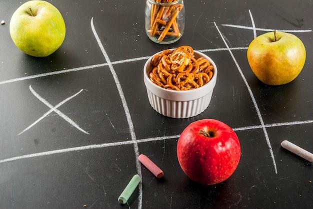 Concepto de merienda poco saludable con galletas, papas fritas y manzanas en pizarra negra