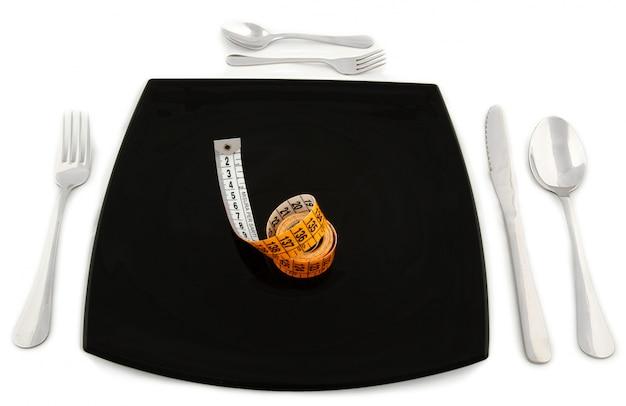 Concepto metafórico con cinta métrica en el plato con cubiertos.