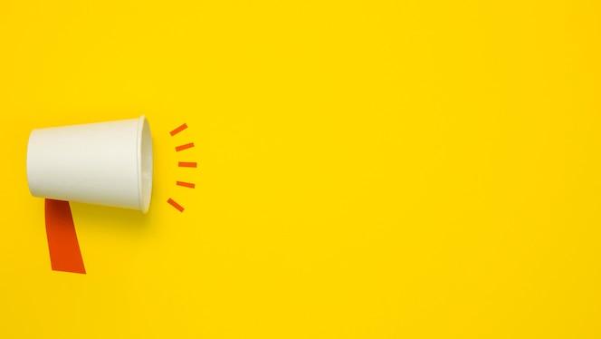Concepto minimalista con megáfono sobre fondo amarillo