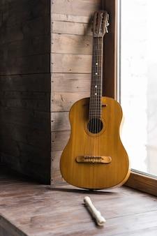 Concepto minimalista con paredes de madera y guitarra clásica.