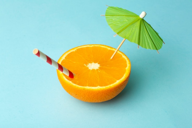 Concepto mínimo de comida de verano. jugo de naranja y jugosas frutas tropicales sobre un fondo de color claro