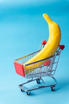 Concepto mínimo de compras. plátano en un carrito de compras de juguete.