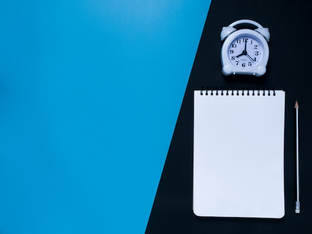 Concepto mínimo de espacio de trabajo azul negro: bloc de notas, lápiz, reloj despertador, vista superior.