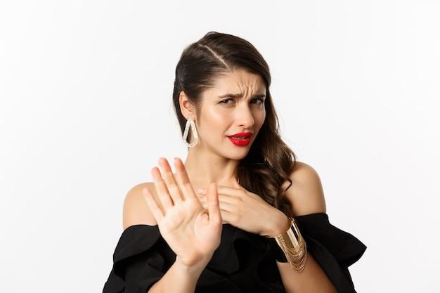 Concepto de moda y belleza. primer plano de mujer joven disgustada en vestido negro diciendo que no, rechazando la oferta y mirando con desdén, de pie sobre fondo blanco.