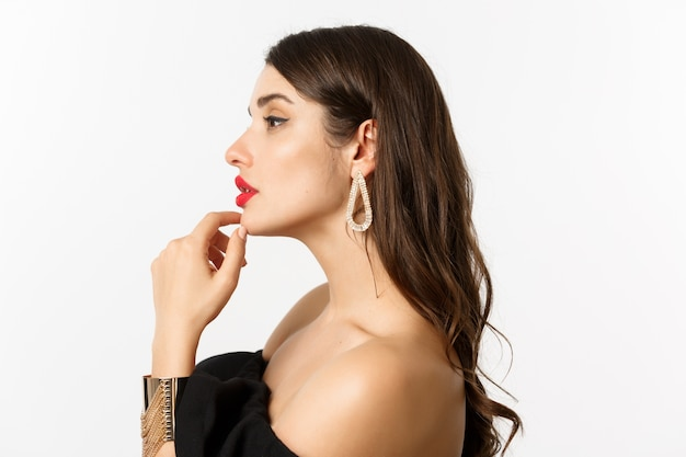 Concepto de moda y belleza. vista de perfil y elegante mujer en vestido de noche negro, maquillaje y aretes, mirando a la izquierda sensual, de pie sobre fondo blanco.