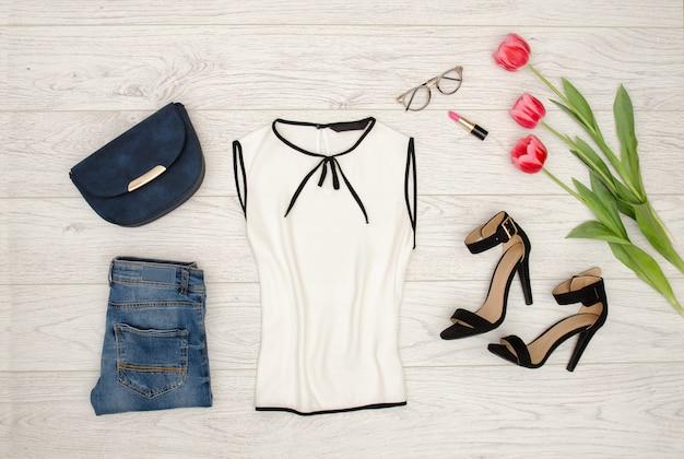 Concepto de moda. blusa blanca, bolso azul, gafas, pintalabios, zapatos negros y tulipanes rosados.