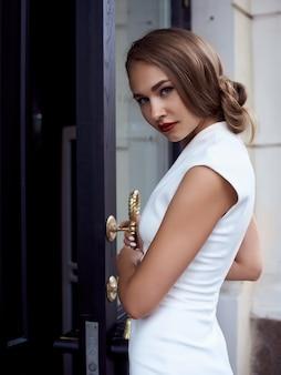 Concepto de la moda de la calle: retrato lleno del cuerpo de la mujer hermosa joven que camina en la ciudad.