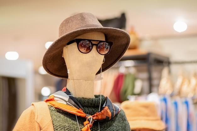 Concepto de moda y compras. maniqui vestido con sombrero y gafas de sol en una tienda de ropa para mujeres