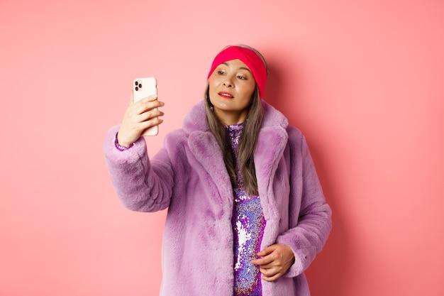 Concepto de moda. elegante mujer asiática senior tomando selfie en smartphone, posando en abrigo de piel sintética púrpura y vestido de fiesta, de pie sobre fondo rosa.