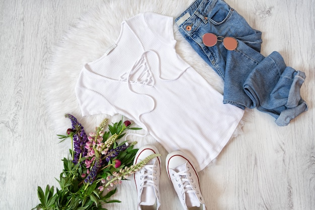 Concepto de moda. estilo callejero. camiseta blanca con cordones, jeans, zapatillas y ramos de flores.