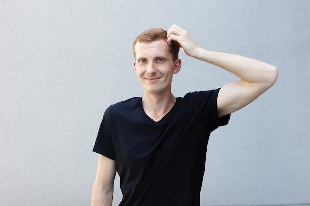 Concepto de moda, estilo, emociones y personas - close up retrato de una pelirroja de un hermoso chico varonil con pecas en una camiseta negra de fondo gris. se rasca la cabeza pensativamente