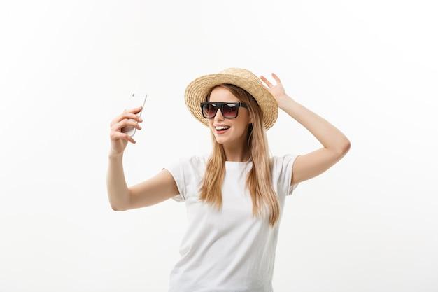 Concepto de moda y estilo de vida: mujer joven y bonita con sombrero, gafas de sol tomando una foto de sí misma por teléfono móvil aislado sobre fondo blanco.