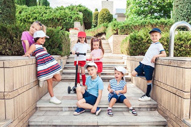 Concepto de moda infantil. grupo de chicos y chicas adolescentes posando en el parque. ropa colorida para niños, estilo de vida, conceptos de colores de moda.