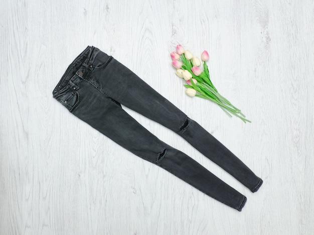 Concepto de moda. jeans rasgados grises y tulipanes rosados.