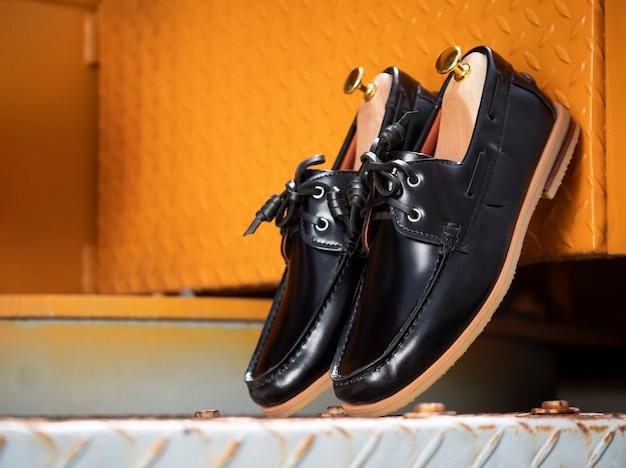 Concepto de moda masculina. zapatos náuticos de cuero negro aislados en amarillo.