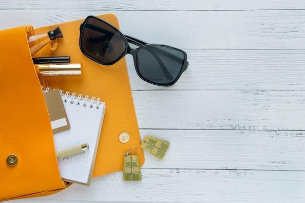 Concepto de la moda productos cosméticos, gafas de sol, cuaderno y bolso naranja.