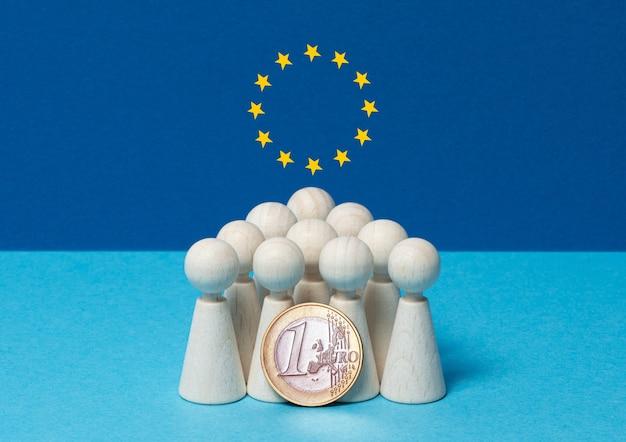 Concepto de moneda única europea figuras de madera sobre fondo azul.