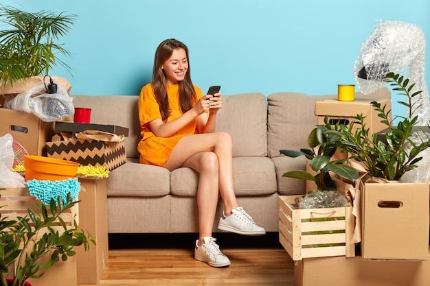 Concepto en movimiento. modelo de mujer joven alegre rodeado de muchas cajas