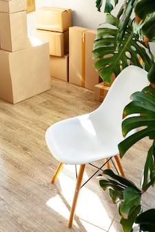 Concepto de mudanza de casa con cajas de cartón apiladas en una habitación