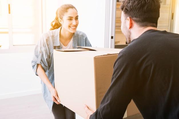 Concepto de mudanza con pareja llevando caja