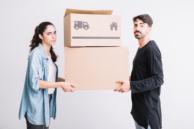 Concepto de mudanza con pareja llevando dos cajas
