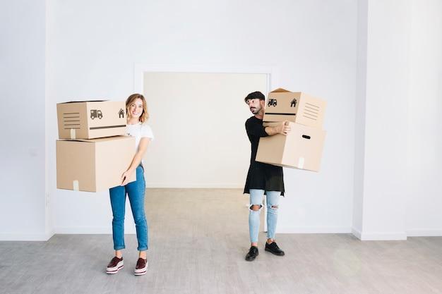 Concepto de mudanza con pareja sujetando cajas