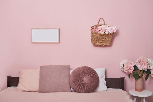 Concepto de muebles de dormitorio interior. acogedor rincón rosa dormitorio. acogedor y femenino dormitorio con cama rosa, cojines decorativos y plantas en un taburete de madera.